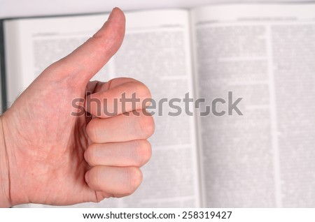 Thumbs up on the background of an open book. - stock photo