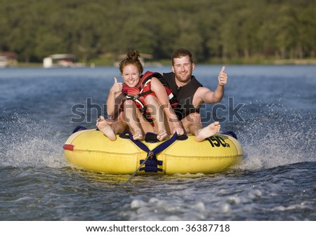 Thumbs up while tubing on a lake - stock photo