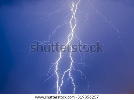 Thunder in the blue night sky with purple effect in the right bottom corner due to city lights  - stock photo