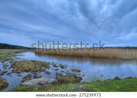 Thunderclouds over the river in the spring. The strong wind and clouds pass on the river. Dark dramatic rain clouds over countryside landscape. Spring in Russia. - stock photo