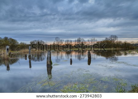 Thunderclouds over the river with the destroyed bridge in the spring. A strong wind and a thunder-storm over the river. - stock photo
