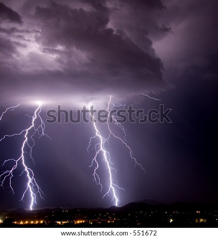 Thundershower and lightning over city and mountains - stock photo