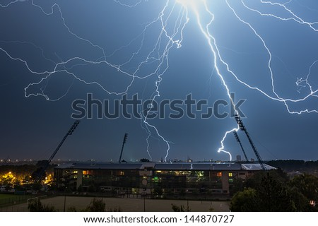 Thunderstorm above a Stadium, in the background is the Skyline of the City Rostock - stock photo