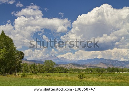 Thunderstorm Clouds building up and boiling over the Colorado Rocky Mountains Longs Peak. - stock photo