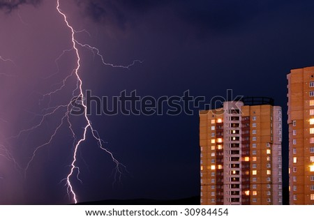 Thunderstorm in the city. The flash of lightning against a background of dark and gloomy sky in the left side of the frame houses. - stock photo