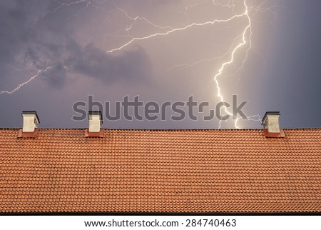 Thunderstorm with lightening, top of the roof at night - stock photo