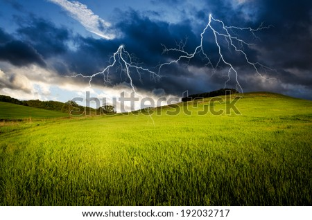 Thunderstorm with lightning in green meadow - stock photo