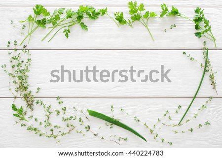 Thyme, parsley and chives frame on white wood flat lay. Top view on herbs put in the form of frame on white wooden background. Copyspace for advertisement - stock photo