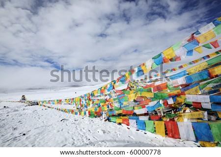 tibetan prayer flags under moody sky, tibet. - stock photo