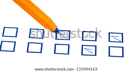 tick in blue square box by yellow plastic pen - stock photo