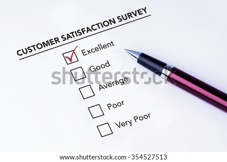 Tick placed in excellent check box on customer service satisfaction survey form with a pen on isolated white background. Business concept survey. - stock photo