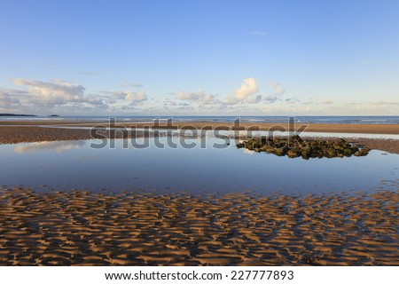 Tidal pool on Traeth Coch empty sandy beach at low tide in Red Wharf Bay, Isle of Anglesey, North Wales, United Kingdom, Great Britain, Europe. - stock photo