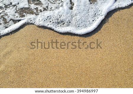 Tidal wave on a clean, sandy, sea beach - stock photo