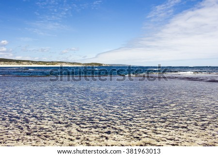 Tide ebbing out from the   famous white sandy  surfing beach  at Margaret River south western Australia  on a calm cloudy afternoon in  early summer . - stock photo