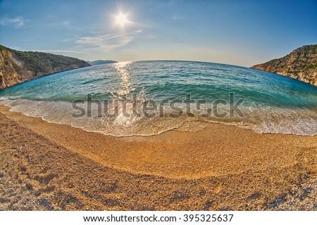 Tide & Wave at Empty Sunset Myrtos Beach in Kefalonia, Greece - stock photo