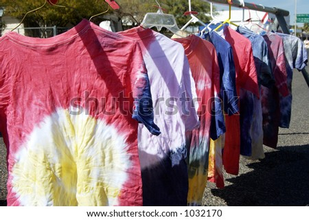 Tie-died shirts drying on hangers at a street fair. - stock photo