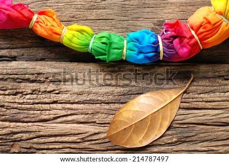 tie dye cloth on wooden table. - stock photo