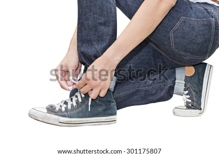Tie his shoes Retro Canvas High Top Sneakers and Regular Fit Straight Leg Jeans isolated on white background, selective focus (detailed close-up shot) - stock photo