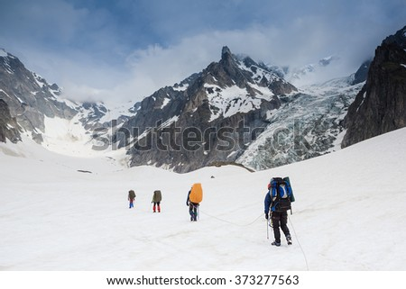 Tied climbers climbing mountain with snow field - stock photo