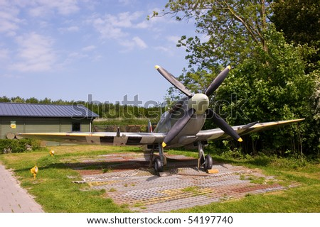 Tied down British Supermarine Spifire in front of shack - stock photo