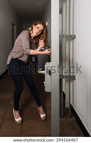 Tied to the office - Attractive business woman is strapped to metal office doors with handcuffs - trying to free herself in panic - stock photo