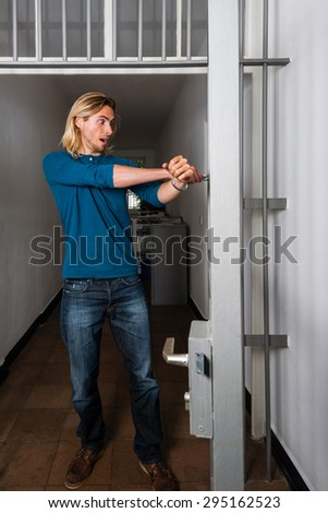 Tied to the office - Young handsome casual business guy  is strapped to metal office doors with handcuffs - trying to free himself in panic - stock photo
