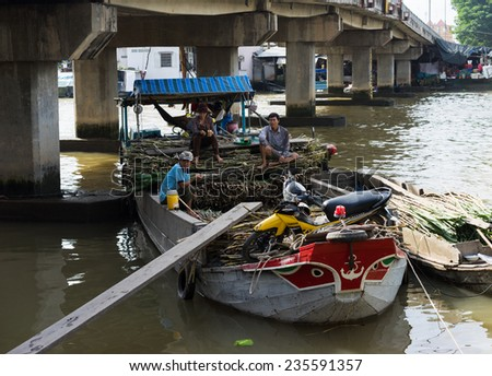 Tien Giang, Vietnam - Nov 28, 2014: Floating boat loaded with sugar cane on sale at Cai Be floating market, one of the busiest market places in Mekong delta - stock photo