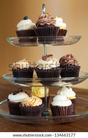 Tiered party serving tray with some decadent gourmet cupcakes frosted in a variety of flavors. - stock photo