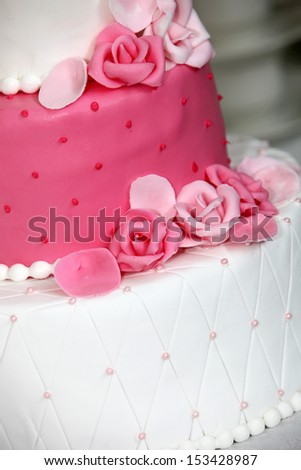 Tiered wedding cake decorated with pink roses made of icing sugar to match the pink and white alternating tiers - stock photo