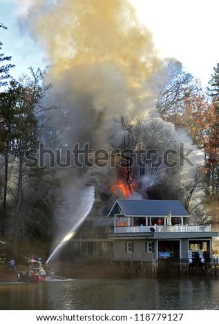 TIGER, GA, USA - NOV. 9: A fire boat on the water spraying a large house, November 9, 2012, on Lake Burton. - stock photo