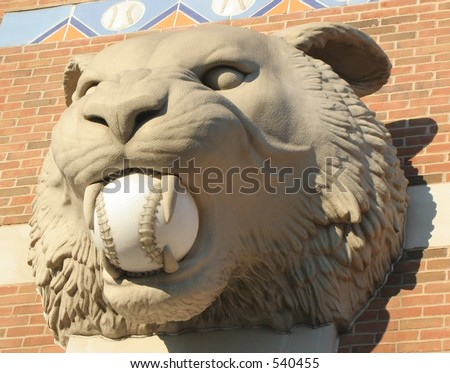 Tiger head statue with baseball in his mouth - stock photo