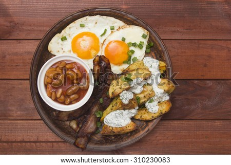 Tight breakfast, baked potatoes, canned beans, bacon and eggs. - stock photo