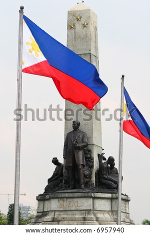 Tight shot of the Rizal monument at Luneta with Philippine flags - stock photo