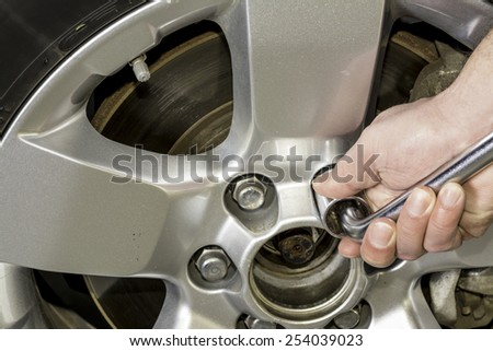 Tightening lug nuts on a truck wheel - stock photo