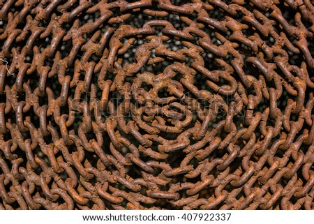 Tightly strung circular rows of rusty chains, close up. - stock photo