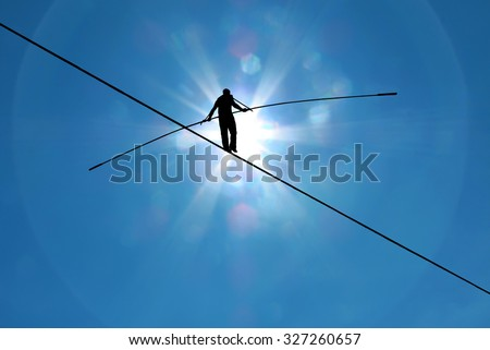 Tightrope walker balancing on the rope concept of risk taking and challenge - stock photo