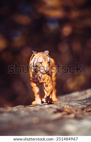 Tigress with a baby between her teeth. Tiger toy figurine in situation on defocused nature background. - stock photo