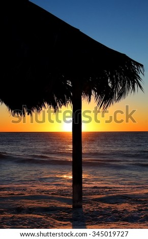 Tiki hut on beach at the sunset with surfer in ocean - stock photo