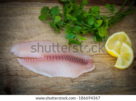 Tilapia fillet with fresh parsley and lemon - stock photo