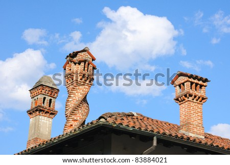 tile roof and chimneys over blue sky - stock photo