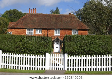 Tiled and brick cottage behind picket fence at Chiddingfold. Surrey. England - stock photo