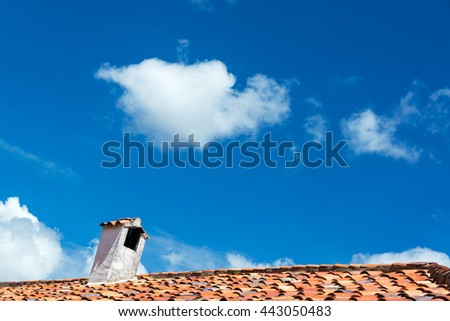 Tiled colonial roof in Villa de Leyva, Colombia with a beautiful blue sky - stock photo