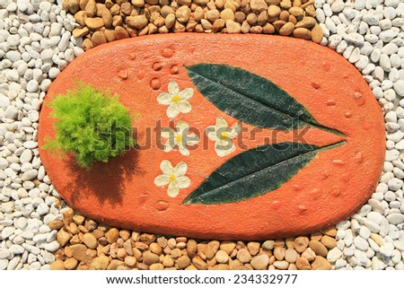 Tiled floor decorated with small plant and painting - stock photo