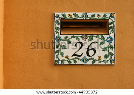 tiled letterbox for home against orange wall - stock photo