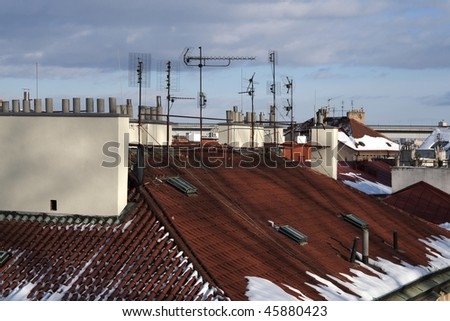 Tiled roof of old town with modern rooftop antennas - stock photo