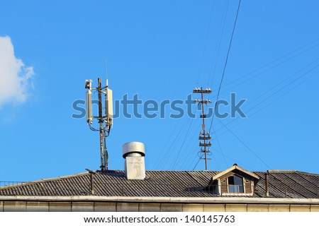 Tiled roof with antennas and a chimney over blue sky - stock photo