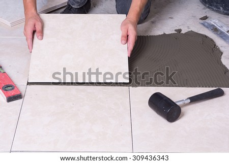 Tiler installing ceramic tiles on a floor . - stock photo
