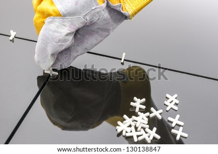 Tilers hand while using spacer for installing a black ceramic tiles. - stock photo