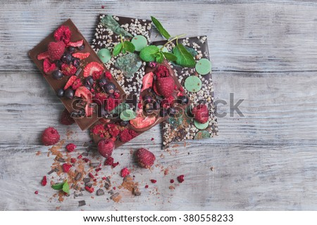 Tiles of a broken exquisite hand-made chocolate with dried and fresh berries, nuts, peel, mint, clean empty place for text, for the recipes - stock photo