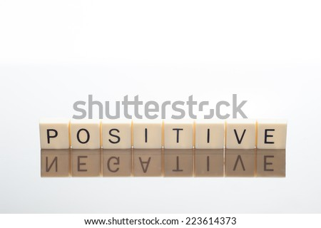 Tiles of letters spell positive but their reflection spells negative - stock photo